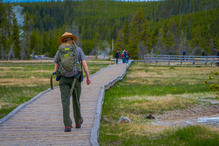 YELLOWSTONE, MONTANA, USA MAY 24, 2018: Outdoor view of female park ranger wearing a green uniform with a backpack, walking along the wooden path in the Old Faithful Upper Geyser Basin Editorial
