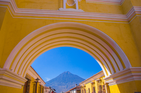 Ciudad de Guatemala, Guatemala, April, 25, 2018: The colorful yellow arch of Antigua city with the active Agua volcano in the background, Guatemala