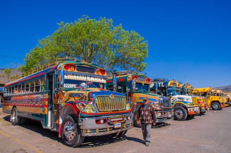 Ciudad de Guatemala, Guatemala, April, 25, 2018: Unidentified man walking in front of Typical guatemalan chicken bus in Antigua, Guatemala, its a name for colorful, modified and decorated bus