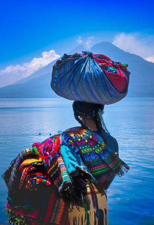 Panajachel, Guatemala -April, 25, 2018: Outdoor view of unidentifed indigenous woman, wearing typical clothes and walking in lakeshore with small boats in Atitlan Lake and volcano in Background in Guatemala