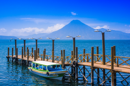 Panajachel, Guatemala -April, 25, 2018: The docks in Panajachel with San Pedro volcano in the background. A few small boats are waiting for tourists in the morning for the Lake Atitlan tour Stok Fotoğraf - 120296063
