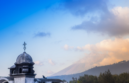 Outdoor view of stoned dome of building in Antigua city with agua volcano mountain behind in a gorgeous sunny day and blue sky in Antigua city in Guatemala.