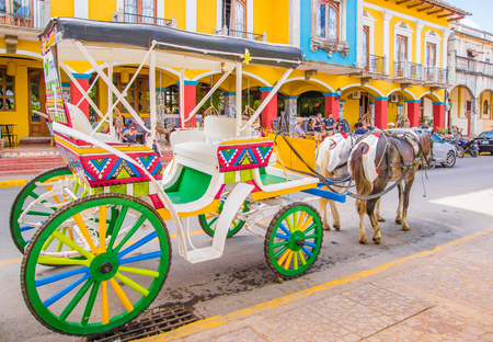 GRANADA, NICARAGUA, MAY, 14, 2018: Outdoor view of colourful decorated horse-drawn carriages for hire by tourists to tour the colonial town
