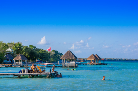 Quintana Roo, Mexico, May, 29, 2018: Unidentified people enjoying from a wooden pier and houses the Laguna Bacalar, Chetumal, Quintana Roo