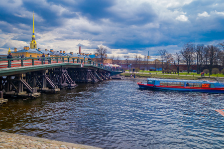 ST. PETERSBURG, RUSSIA, 01 MAY 2018: Outdoor view of floating house close to a wooden bridge and people walking around the city enjoying the gorgeous sunny day in Saint Petersburg