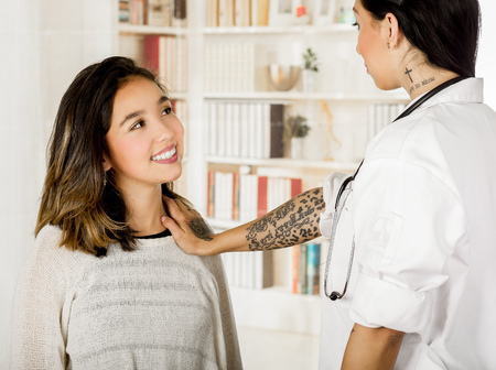 Beautiful tattooed young doctor using her hand checking the chest of the patient, in office background