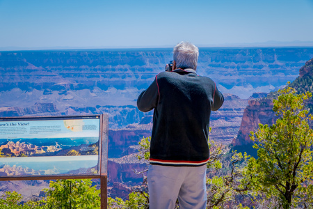 Grand Canyon,Arizona USA, JUNE, 14, 2018: Unidentified old man taking pictures of the gorgeous Bright Angel canyon, close to an informative sign, major tributary of the Grand Canyon