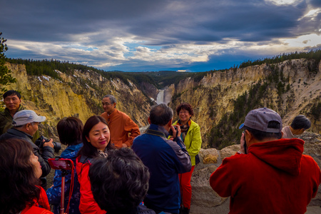 YELLOWSTONE NATIONAL PARK, WYOMING, USA - JUNE 07, 2018: Unidentified tourists taking pictures of the beautiful upper fall in Yellowstone National Park, Wyoming