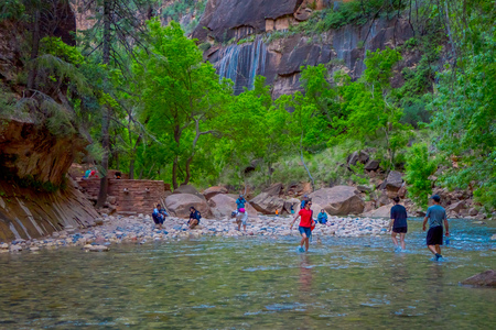 ZION, UTAH, USA - JUNE 14, 2018: Outdoor view of unidentified people hiking in zion narrow with virgin river in summer season, in Zion National park, Utah USA.