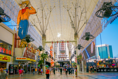 Las Vegas, NV, USA, June 15, 2018: Tourists outside the Pioneer Cowboy Vegas Vic neon sign watch the Freemont Street Experience light show. The canopy was installed in 1995