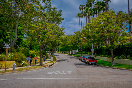 Los Angeles, California, USA, JUNE, 15, 2018: Palm trees street in Beverly Hills and cars circulating in the roads of Los Angeles, California, USA, is famous avenue and celebrities homes Editorial
