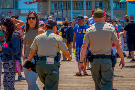 Los Angeles, California, USA, JUNE, 15, 2018: Outdoor view od people and police walking at the pier with the end of Route 66 in Santa Monica. The amusement park is a world famous tourist attraction