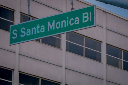 Los Angeles, California, USA, JUNE, 15, 2018: Outdoor view of green styled Santa Monica Boulevard road sign with a building background defocused Editorial