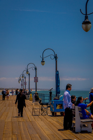 Los Angeles, California, USA, JUNE, 15, 2018: Unidentified people sitting in a wooden bench chair on the bridge overseeing Santa Monica Beach in California USA during sunny day Editorial