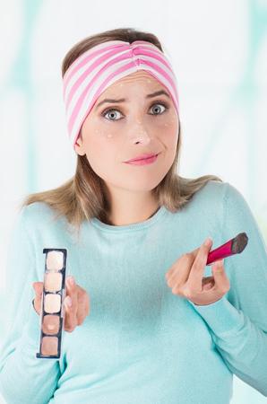 Gros plan d'une jeune femme inquiète tenant une palette de maquillage et faire du maquillage fou sur son visage à l'aide d'un pinceau de maquillage, dans un arrière-plan flou Banque d'images