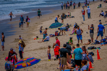 Los Angeles, California, USA, JUNE, 15, 2018: Outdoor view of unidentified people visit the beach and enjoying and walking in the sand in Santa Monica, California