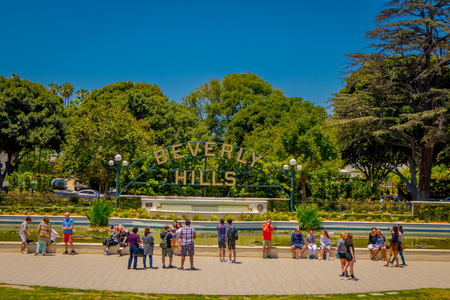 Los Angeles, California, USA, AUGUST, 20, 2018: Outdoor view of unidentified people taking pictures and posing in front of Beverly Hills sign and fountain