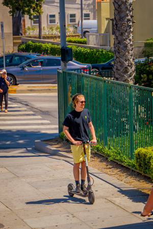 Los Angeles, California, USA, JUNE, 15, 2018: Outdoor view of unidentified teen using a scooter at Venice Beach in Santa Monica, popular by domestic residents for relaxing and sporting in California. Editorial