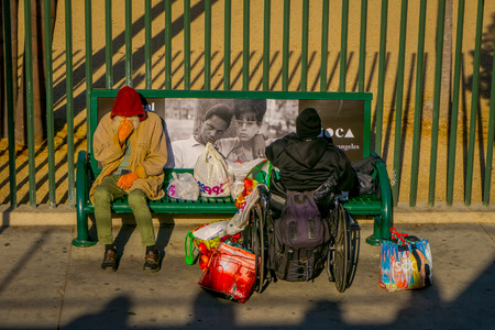 Los Angeles, California, USA, AUGUST, 20, 2018: Outdoor view of homeless couple on a park bench, woman in a wheel chair in Los Angeles, California Editorial