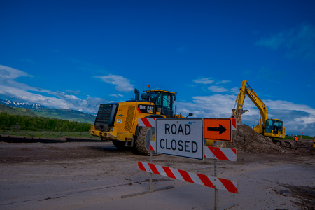 YELLOWSTONE NATIONAL PARK, WYOMING, USA - JUNE 07, 2018: Informative sign of road closed with equipment parked in a construction zone in Yellowstone National Park