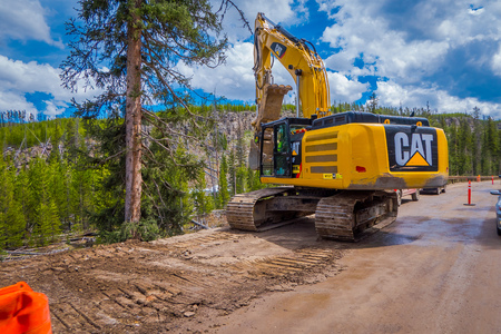 YELLOWSTONE NATIONAL PARK, WYOMING, USA - JUNE 07, 2018: Outdoor view of truck removing soil in a road in construction during a gorgeous day. Roadwork in Yellowstone National Park