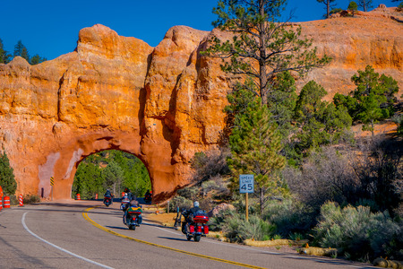 BRYCE CANYON, UTAH, JUNE, 07, 2018: Outdoor view of motorcyclists in the road crossing throught the red arch road tunnel on the way to Bryce Canyon National Park, Utah