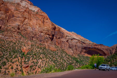 ZION, UTAH, USA - JUNE 12, 2018: Unidentified man taking pictures from the asphalt to the picturesque mountains of orange and red sandstone