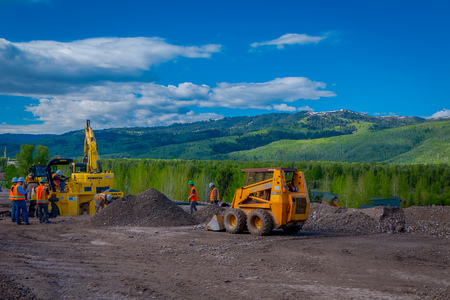 YELLOWSTONE NATIONAL PARK, WYOMING, USA - JUNE 07, 2018: Unidentified people working in a road construction equipment parked in a construction zone. Roadwork in Yellowstone National Park