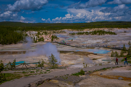 YELLOWSTONE, MONTANA, USA MAY 24, 2018: Above view of people walking in the boardwalk among pools and geysers, porcelain basin of Norris Geyser Basin, Yellowstone National Park, Wyoming Editorial