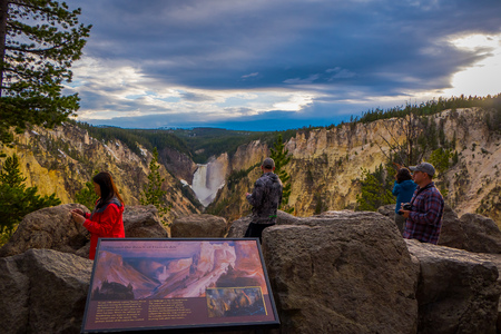 YELLOWSTONE NATIONAL PARK, WYOMING, USA - JUNE 07, 2018: Outdoor view of informative sign with tousits using their devices to take pictures of the landscape in Yellowstone National Park, Wyoming