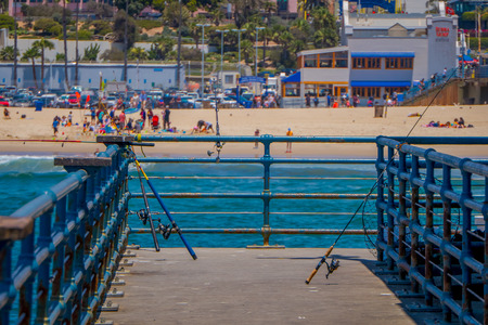 Los Angeles, California, USA, JUNE, 15, 2018: Outdoor view of fishing rods standing in a wooden pier used for people that usually fishing in the pier of Santa Monica Sajtókép