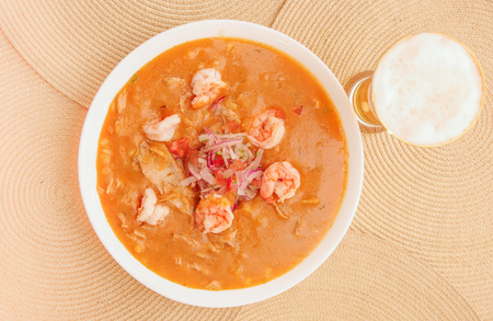 Above view of Ecuadorian food: shrimp cebiche with a glass of beer in wooden table background.
