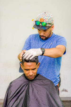 QUITO, ECUADOR, AUGUST 21, 2018: Outdoor view of unidentified man wearing gloves and hat, using a cut hair machine in a youg guy, inside of a refuge for Venezuelan people