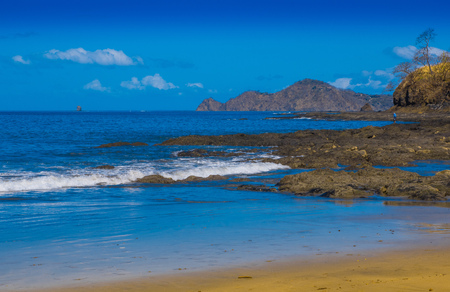 Beautiful outdoor view of of gorgeous rocky beach in Playa hermosa with blue water and beautiful sunny day with blue sky