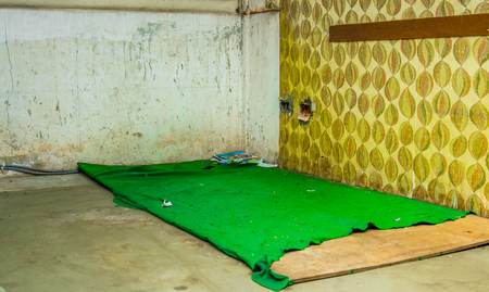 Indoor view of a room inside of a refuge center with a green blanket in the ground, from people that escape from their country Venezuela
