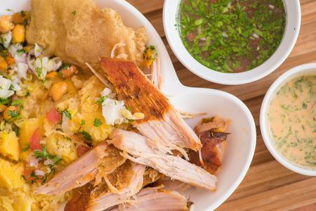 Cerca de delicioso hornado con puré de papas con ensalada, tostado y mote con dos cuencos pequeños con salsa verde y rosa, comida típica andina ecuatoriana en fondo de madera.