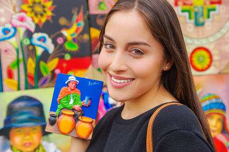 Smiling woman holding a souvenir in a shopstore in Banos, Ecuador. Banos is a small touristy town, which is mainly known for its various outdoor acitivities Stock Photo