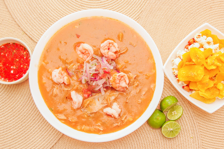 Above view of Ecuadorian food: shrimp cebiche with some chifles inside white bowl, lemon and red spicy salad inside a white bowl in a wooden table background. Stock Photo