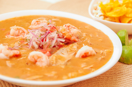 Close up of selective focus of Ecuadorian food: shrimp cebiche with some blurred chifles background. Stock Photo