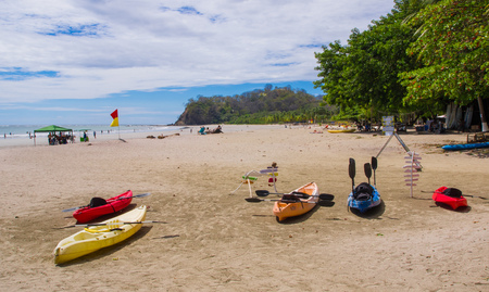 Samara, Costa Rica, June, 26, 2018: Outdoor view of colorful kayaks on the tropical beach of Samara in rental shop rady for intrepid tourists that love adventure in a gorgeous sunny day Sajtókép