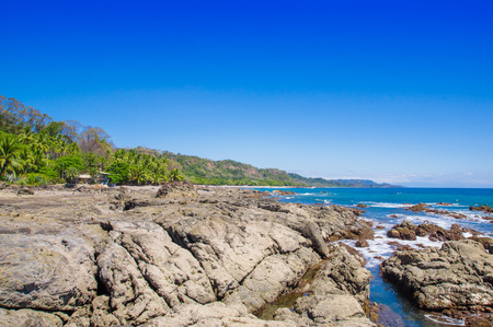 Beautiful view of beach with rock formations in the ocean with waves approaching and blue sky near sand and forest in gorgeous blue sky and sunny day with blue sky in Playa Montezuma, Costa Rica Stock Photo