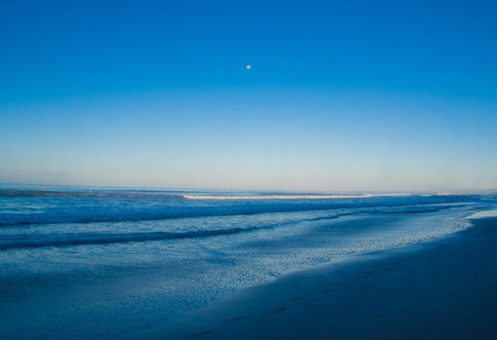 Ashtonishing view of waves, sand beach in a gorgeous sunny day on Santa Teresa beach with a moon in the blue sky in Costa Rica. Stock Photo