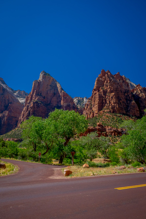 Beautiful view of red asphalt scenic road among the picturesque mountains of orange and red sandstone in a gorgeous sunny day and blue sky in Zion National Park in USA. Stock Photo