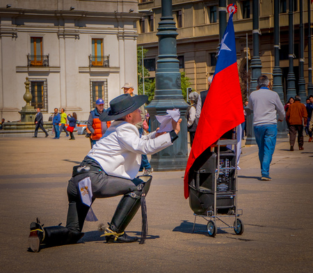 SANTIAGO, CHILE - SEPTEMBER 13, 2018: Outdoor view of unidentified man wearing boots, white t-shirt and black pants oh his knees in Armas square in front of a Chilean flag in Santiago, Chile
