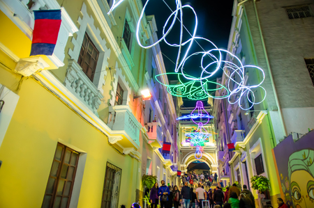QUITO, ECUADOR- AUGUST, 15, 2018: Crowd of people walking in a tight street during a spectacle of lights projected on the walls with some illuminated figures during the Quito light festival