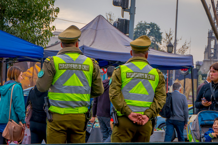 SANTIAGO, CHILE - SEPTEMBER 13, 2018: Back view of two Police called as carabineros checking the crowd for segurity in front of la Moneda Palace, seat of the President in Santiago Éditoriale