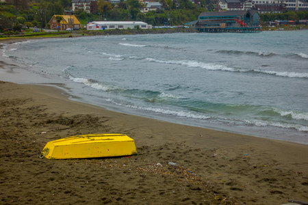 Outdoor view of small yellow boat laying down in the sandy beach of Puerto Varas in Chile, during coudy day. Stock Photo