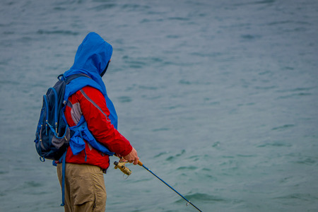 Close up of fisherman wearing a backpack with a fishing rod, in sunny cold day in Puerto Varas in Chile.