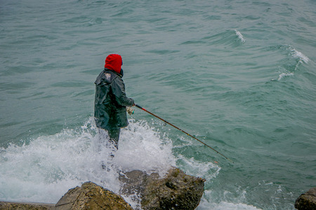 Unidentified fisherman standing in a rock with a fishing rod on chilean patagonia in Chile. Stock Photo