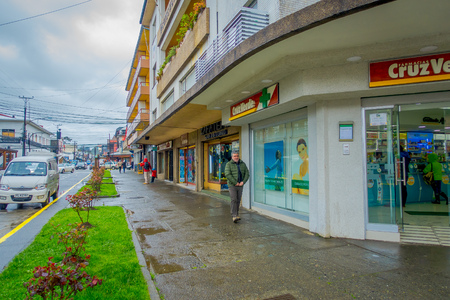 PUERTO VARAS, CHILE, SEPTEMBER, 23, 2018: Unidentified man walking close to a buildings, protecting from rain in Puerto Varas in Chile